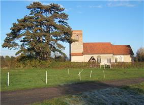 A stone church seen from the south with red tiled roofs and a plain tower on the left