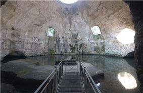 Bare concrete dome interior today called the Temple of Mercury with two square windows half-way up the dome on the far side, a circular oculus at the top, and a water level that reaches up to the base of the dome