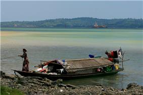 Sama-Bajau woman anchoring a family boat (banglo) in Malaysia