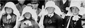 Four women wearing large white bonnets