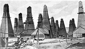 A black-and-white photograph showing a field of derricks each completely enclosed within its own oddly shaped wooden building.