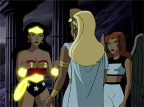 Wonder Woman (left) having additional features of her costume activated by Hippolyta (center). Hawkgirl, not in costume, watches from the right.