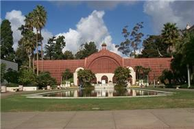 Photograph of the Botanic Building, one of several buildings in Balboa Park. A red conservatory building, it is fronted by a reflecting pool and surrounded by multiple species of trees.