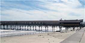 A long building built on a narrow pier extending out from the beach to the ocean.