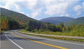 A paved highway with double-yellow centerline, shoulders and a guardrail on the far side curves across the foreground. In the distance is a high, flat-topped mountain covered in woods, with some trees showing early autumn color, framed by similar slopes on either side. Above the landscape is a blue sky with clouds.