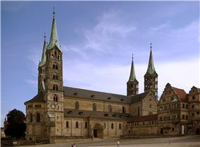 A stone cathedral with two towers on the west façade and two towers flanking the choir, all four towers are topped with slender, pointed metal roofs.