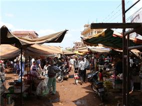 Outdoor market stalls on red earth, with makeshift cloth roofs