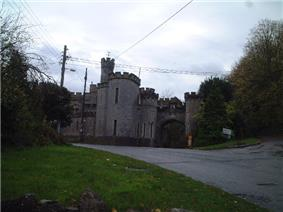 Stone building with slit windows and battlements. Foreground is road with grass verges.