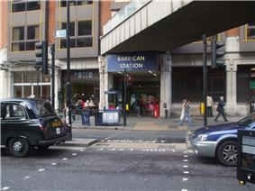 Across a road with a London taxi and a car is an entrance. This has people standing in it and above is a blue rectangular sign reading