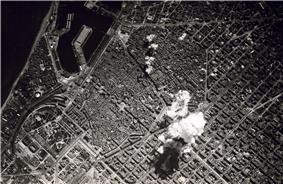 Black-and-white photo of the city from high above. Smoke from a bomb can be seen