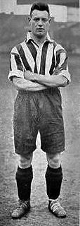 A man standing with his arms crossed, while wearing a vertical striped shirt and long dark shorts.