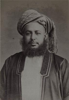 A black-and-white photograph of a man with a dark beard wearing a turban, a dark jacket, a shirt, and a belt, sitting in a chair, and looking at the viewer