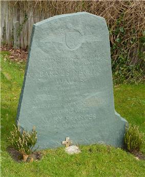 Irregular green gravestone standing in a grassy churchyard