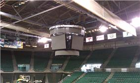 Arena scoreboard hanging in an empty venue with banners and seats visible