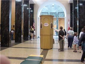 A large hall flanked by black marble columns on the left and right. There is a wooden tower in the middle on which are mounted several plaques. Two people are standing at the tower; one, obscured behind the other, points at a plaque while other people mill about on the sides of the room. The far end opens into a lighted rotunda.