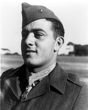 Head of a young white man in a plain dark jacket with a star-shaped medal hanging from a ribbon around his neck. His garrison cap is tilted to the side and has a single round pin on its side.