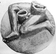 Black-and-white photograph of a statue consisting of an inscribed, round pedestal on top of which sits a seated, nude, male figure of which only the legs and lower torso are preserved