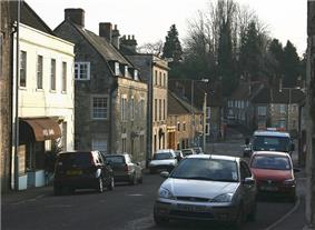 Street scene showing brown stone houses with tiled roofs. Several parked cars in the road.