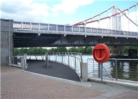 Start of a footbridge that curves under one end of a suspension bridge, along the bank of a wide river.