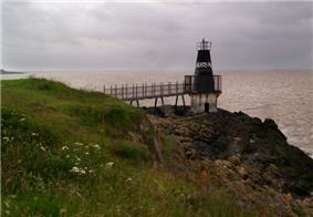 Metal lighthouse reached by walkway from land.