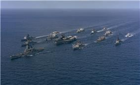 A large collection of ships sailing on the sea from the back right to the front left. At the center of the cluster of ships is an aircraft carrier, with a battleship in front of the carrier. Other ships of various types are sailing in a roughly circular formation to provide defense for the aircraft carrier.