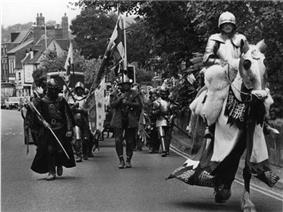 An armoured and mounted man leads a small party, similarly dressed in mediaeval attire, along a road.