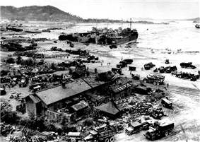 A village by a beach filled with landing craft, vehicles, and troops from a recently landed force