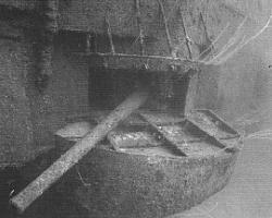 Underwater photograph of a gun protruding from an opening in the side of a sunken ship.