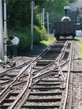 A rail track recedes into the distance where a steam train stands; the track has three rails, the middle of which is offset to the right in the foreground but switches to the left in the middle at some complex pointwork where three other rails join from the left
