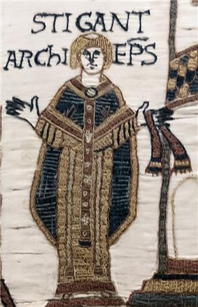 A standing tonsured man with his arms outstretched wearing clerical robes.