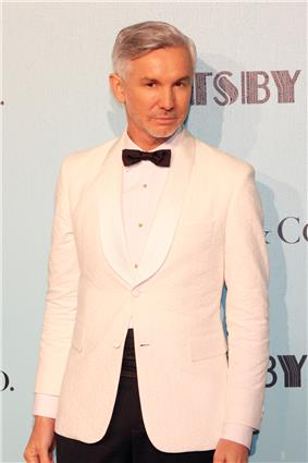 A male with grey hair is seen standing in front of a white wall with black text. He is wearing a white jacket on top of a white shirt with a black bow tie shirt.