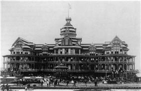 A black-and-white photograph of a grand beach-side hotel