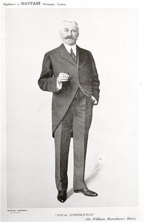 A well-dressed man with greying hair and a large moustache stands looking directly at the camera. In his right hand is a cigar.