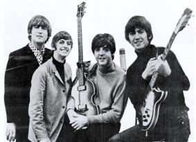A black and white photograph of the Beatles holding their guitars.