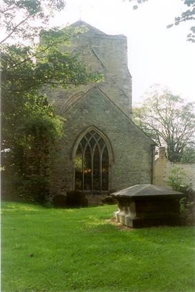 Photograph showing an old stone church with a short wide tower. The view is taken from a graveyard, there is a large tomb stone in the foreground and the church is surrounded by trees.