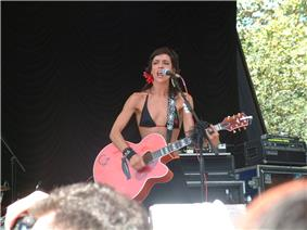A man on a stage, wearing a black bikini top and skirt. She is standing behind a microphone stand and holding an acoustic guitar.