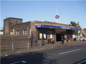 A red-bricked building with five people standing in front of it and a blue sign reading