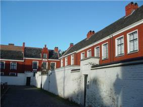 A series of red houses with dark roofs are partially hidden behind a white, deteriorating wall.