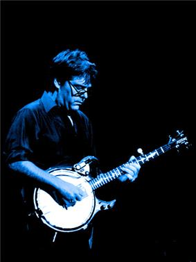 A man wearing a dress shirt and glasses, playing a banjo. A light is shining down on him from above, casting a blue shade over him.