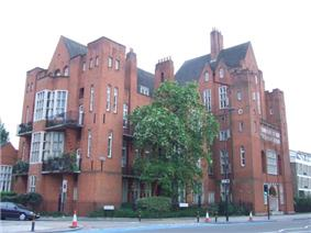 A large red brick building with steep slate covered roofs