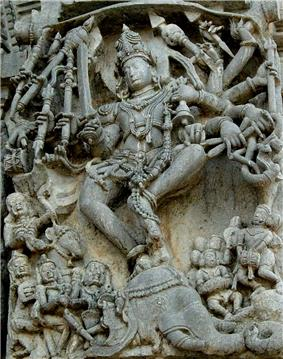 Relief sculpture of deity with 10 arms and people below
