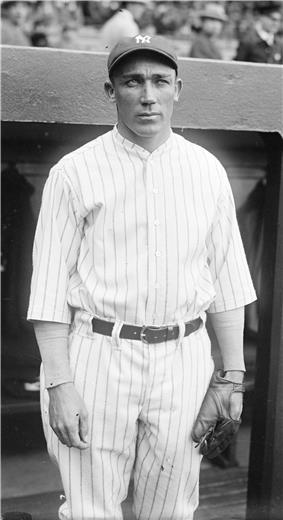 Three-quarter-length picture of a man in a stadium. He wears a striped baseball uniform, a cap with the NY logo, and a baseball glove. He has a long face and tanned complexion with deepset eyes under a heavy brow, and has a small full mouth. He looks out towards the field with a calculating expression, his eyes narrowed and his jaw clenched.