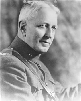 A black and white image of Ben Fuller, a white male in his Marine Corps dress uniform. He has white hair and is not wearing a hat. The background is cloudy and the outside edges of the picture are grayed out.