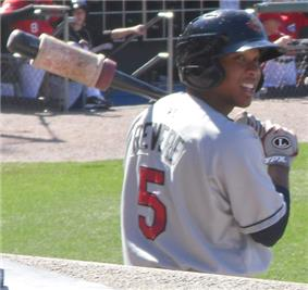 A black man rests his bat, which has a white weight on its barrel, on his shoulder and looks off into the distance while waiting in the on deck circle awaiting his turn to hit
