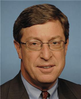 A man with brown hair and glasses wearing a black jacket, gray shirt, and red patterned tie