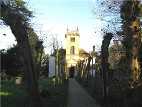 Yellow stone building with prominent square tower. Trees to left and right of the path leading to the building.