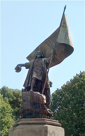 A photograph of a park in which stands a large statue depicting a bearded man standing on a rock who is dressed in a long coat and holding a hat in his right hand, while his left hand grasps a large banner
