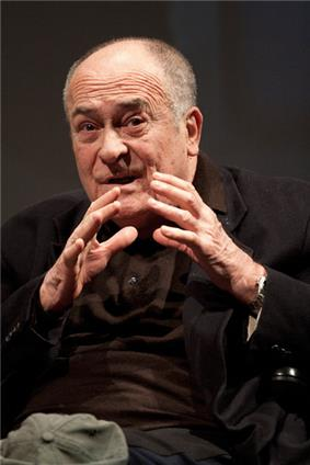 Photo of a balding Italian male with his hands nearly clasped in front of his face. He is wearing a brown unbuttoned collared shirt underneath a black coat.
