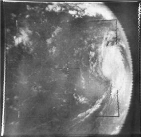 Grayscale image of a tropical cyclone as viewed from space. Due to the position of the camera, the tropical cyclone is at center-right, with banding features visible. As a result of the camera angle, the limb of the Earth is clearly visible; outer space appears a uniform dark gray.