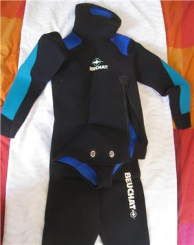 Jacket and trousers of a wetsuit displayed on a cloth, The jacket has a beavertail crotch strap with metal twistlock fasteners.